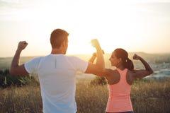 Couples des coureurs lexing des biceps vers le soleil Photographie stock