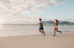 Couples des coureurs sur la plage Images libres de droits