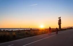 Couples des cyclistes de montagne dans le coucher du soleil Image stock
