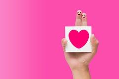 Couples des doigts avec la note se tenante souriante peinte Photographie stock libre de droits