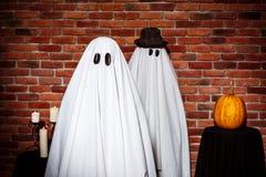 Couples des fantômes posant au-dessus du fond de brique Réception de Veille de la toussaint Photographie stock