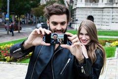 Couples des hippies ayant l'amusement avec la photographie de Smartphone Photo stock