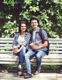 Couples des hippies de déplacement s'asseyant sur le banc Images stock