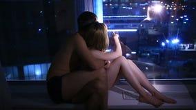 Couples des hommes enamourés et de la femme s'asseyant par la fenêtre la nuit et regardant la ville de nuit clips vidéos