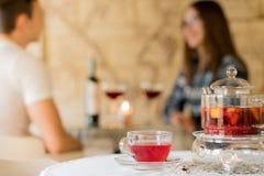 Couples des jeunes dans le restaurant pour un verre de vin Photos stock