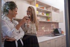 Couples des jeunes femmes élégantes dans la cuisine moderne, vin potable Photographie stock