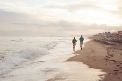 Couples des jeunes hommes pulsant sur le bord de mer Images libres de droits