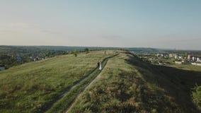 Couples des jeunes marchant le soir d'été de coucher du soleil dans le domaine ; vue aérienne banque de vidéos