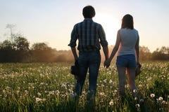Couples des jeunes marchant le soir de ressort de coucher du soleil dans a Photo stock