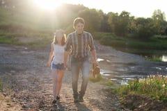 Couples des jeunes marchant le soir de ressort de coucher du soleil dans a Image libre de droits