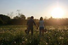 Couples des jeunes marchant le soir de ressort de coucher du soleil dans a Photographie stock libre de droits