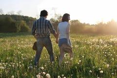 Couples des jeunes marchant le soir de ressort de coucher du soleil dans a Photographie stock