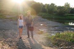 Couples des jeunes marchant le soir de ressort de coucher du soleil dans a Photo libre de droits