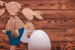 Couples des lapins de Pâques en bois près du grand oeuf avec le copyspace Image libre de droits