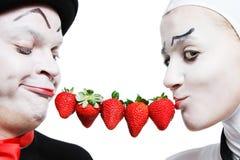 Couples des pantomimes avec la fraise sur un Ba blanc Photo stock