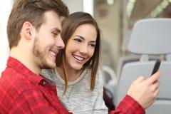 Couples des passagers partageant un téléphone intelligent à l'intérieur d'un train Photographie stock libre de droits