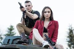 Couples des personnes s'asseyant sur le réservoir avec l'arme à feu Photos libres de droits