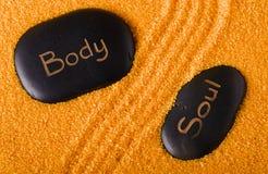 Couples des pierres noires de lave dans à sable jaune Images libres de droits