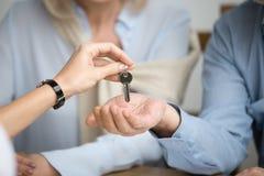 Couples des propriétaires d'une maison obtenant la clé à la nouvelle maison de l'agent immobilier Photographie stock