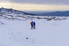 Couples des randonneurs dans les montagnes d'hiver photos libres de droits