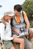 Couples des randonneurs regardant la carte Photo stock