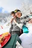 Couples des skieurs prenant un brealk de déjeuner sur les pentes Photos libres de droits