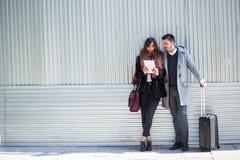Couples des touristes à l'aide de la tablette dans la rue image libre de droits