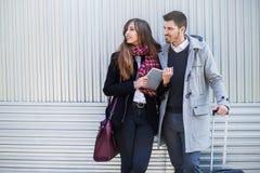 Couples des touristes à l'aide de la tablette dans la rue Image stock