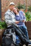Couples des touristes attirants à l'aide du comprimé pendant une pause image libre de droits