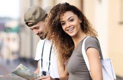 Couples des touristes faisant un tour dans une rue de ville dans un jour ensoleillé Image stock