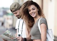 Couples des touristes faisant un tour dans une rue de ville dans un jour ensoleillé Images stock