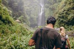 Couples des touristes marchant vers une cascade dans la forêt Images stock