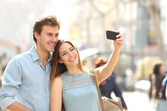 Couples des touristes photographiant un selfie dans une rue de ville photographie stock