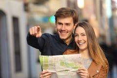 Couples des touristes recherchant une rue dans une carte Photo stock