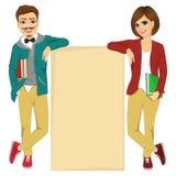Couples des étudiants universitaires se penchant contre un conseil vide Images stock