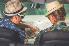 Couples des types s'asseyant dans la voiture et regardant la carte pour trouver la bonne direction Images stock