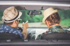Couples des types s'asseyant dans la voiture et regardant la carte pour trouver la bonne direction Image libre de droits