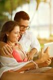 Couples des vacances communiquant avec la famille au-dessus du PC de comprimé Photos stock