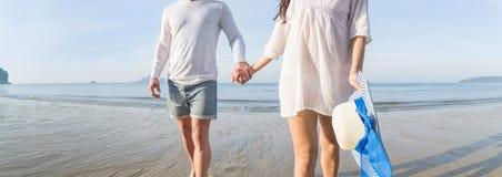 Couples des vacances d'été de plage, beaux jeunes heureux dans l'amour marchant, sourire de femme d'homme tenant des mains Image stock