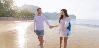 Couples des vacances d'été de plage, beaux jeunes heureux dans l'amour marchant, sourire de femme d'homme tenant des mains Photos stock