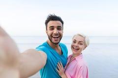 Couples des vacances d'été de plage, beaux jeunes heureux prenant la photo de Selfie, mer d'étreinte de femme d'homme Image stock