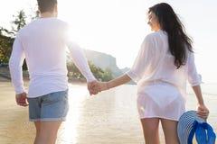 Couples des vacances d'été de plage, les beaux jeunes dans l'amour marchant, femme d'homme tenant des mains Photos libres de droits