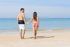 Couples des vacances d'été de plage, les jeunes dans l'amour marchant, femme d'homme tenant l'océan de mer de mains Photographie stock libre de droits