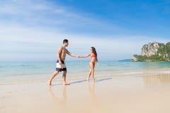 Couples des vacances d'été de plage, les jeunes dans l'amour marchant, femme d'homme tenant l'océan de mer de mains Photos libres de droits