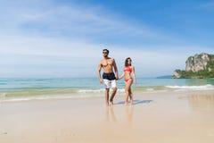 Couples des vacances d'été de plage, les jeunes dans l'amour marchant, femme d'homme tenant l'océan de mer de mains Photographie stock