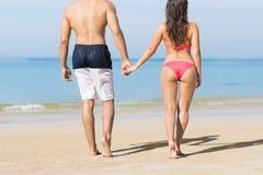 Couples des vacances d'été de plage, les jeunes dans l'amour marchant, femme d'homme tenant l'océan de mer de mains Photos stock