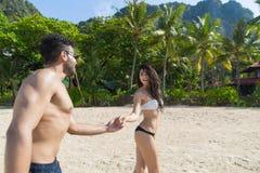 Couples des vacances d'été de plage, les jeunes dans l'amour marchant, femme d'homme tenant la station de vacances d'océan de mer Photos stock