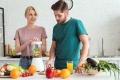couples des vegans préparant le jus de légumes avec le presse-fruits image stock