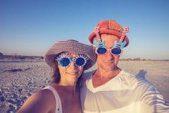 Couples des voyageurs dans des lunettes de soleil drôles prenant le selfie Photographie stock libre de droits