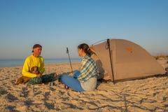 Couples des voyageurs s'asseyant à côté d'une tente Image libre de droits